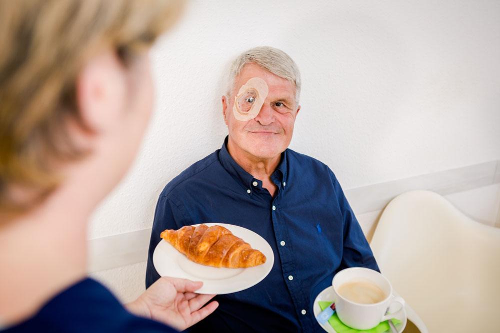 Patient nach Katarakt Operation mit Augenklappe bekommt einen Croissant und einen Kaffee gereicht