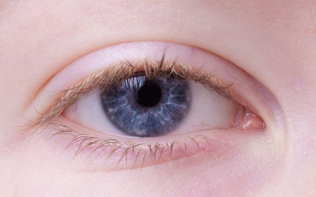Nahaufnahme eines blauen Auges und heller Haut