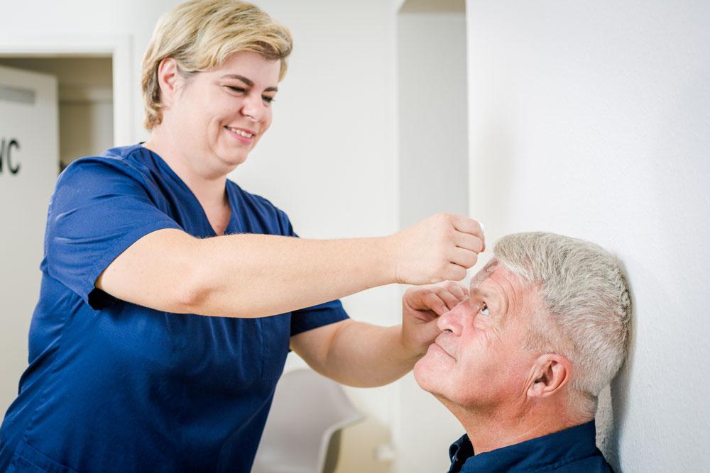 Eine Mitarbeiterin tropft einem Patienten Augentropfen