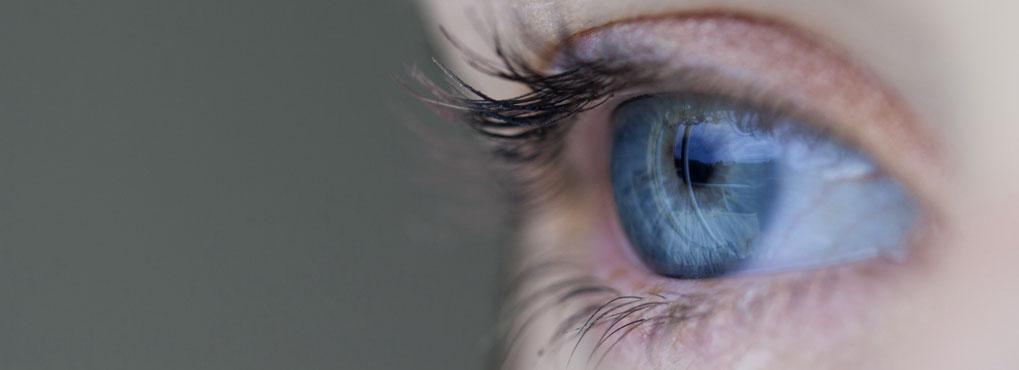 Nahaufnahme eines Auges mit grauem Hintergrund