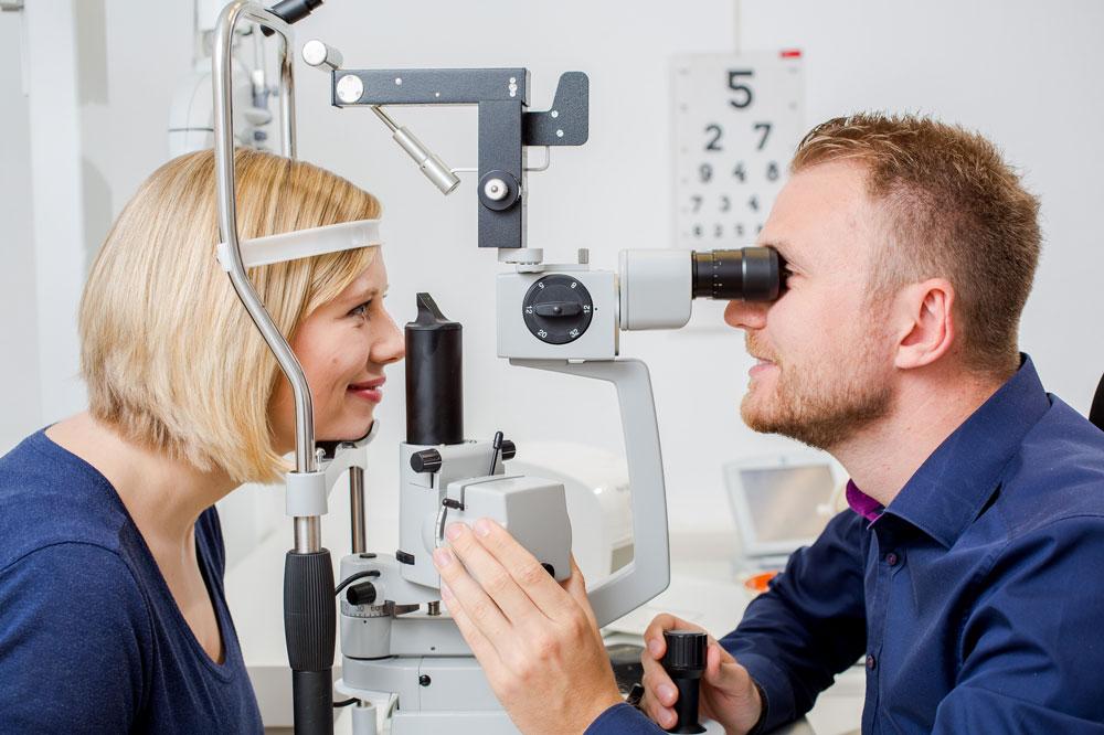 Optometrist untersucht junge Patientin an der Spaltlampe