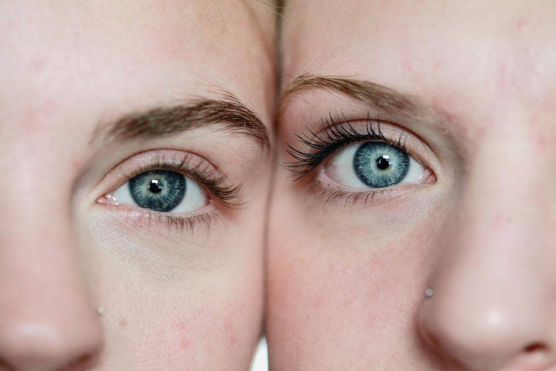 Nahaufnahme von zwei sich berührenden Gesichtern mit blauen Augen