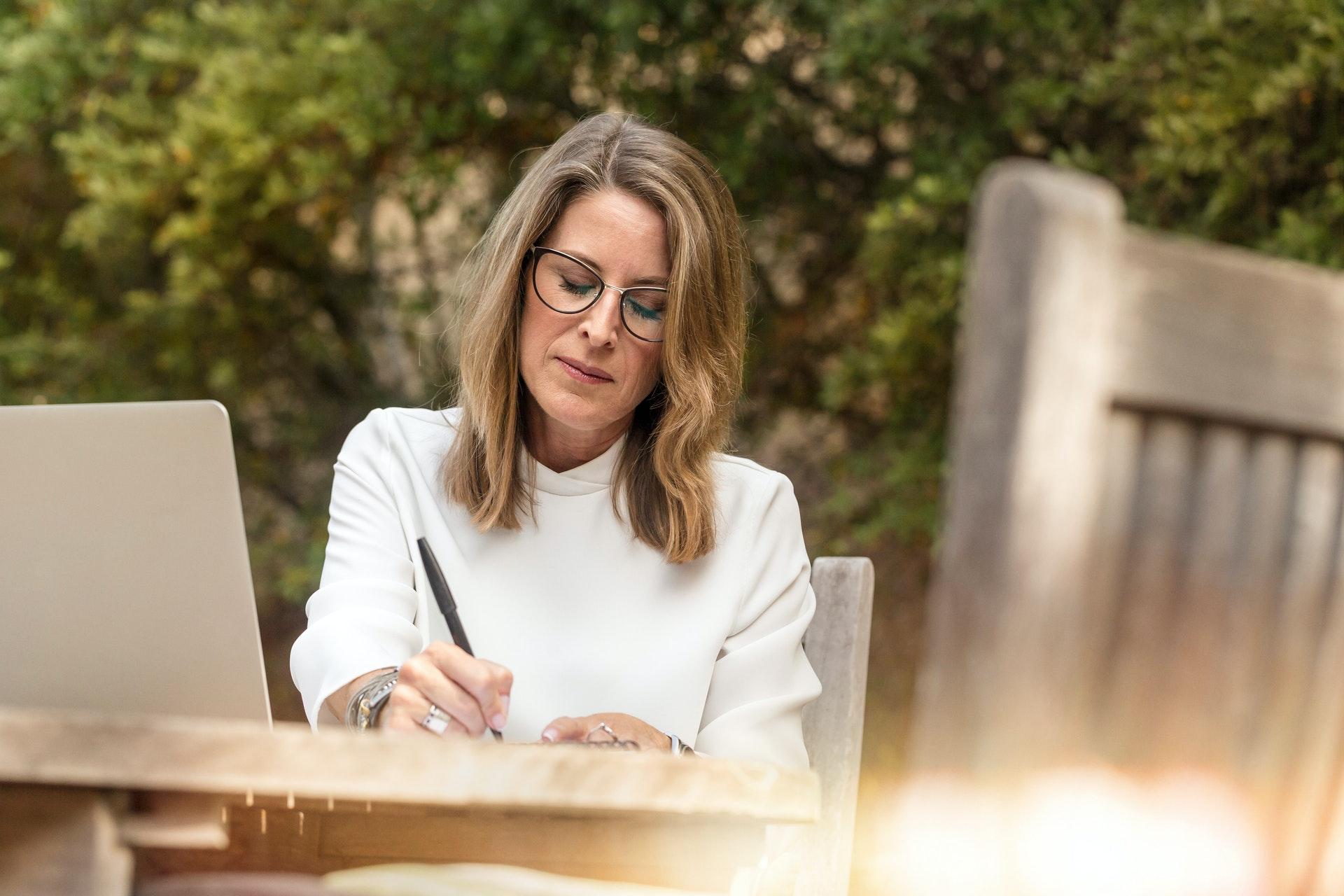 Eine Frau mit geschlossenen Augen sitzt an einem Tisch