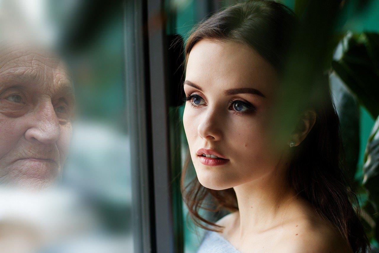 Eine junge Frau die in ihrem Spiegelbild eine alte Frau erkennt